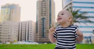 Το παιδί κάθεται στη χλόη στο χτύπημα καλοκαιριού και γέλιου απόθεμα βίντεο