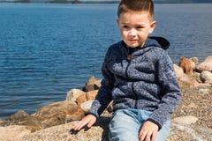 Το παιδί κάθεται τους βράχους κοντά στη θάλασσα στη Φινλανδία Το νέες όμορφες αγόρι και η φύση, Σκανδιναβός κοιτάζουν Στοκ εικόνα με δικαίωμα ελεύθερης χρήσης