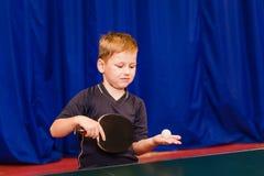 Το παιδί κάνει να αρχειοθετήσει στην επιτραπέζια αντισφαίριση στο εσωτερικό στοκ φωτογραφίες