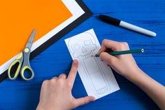 Το παιδί κάνει τα οδοντωτά παιχνίδια εγγράφου για αποκριές Βήμα 3 στοκ φωτογραφία