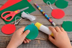 Το παιδί κάνει τις σφαίρες Χριστουγέννων από το χαρτόνι Το παιδί χαράζει και κολλά τις σφαίρες Χριστουγέννων από το χαρτόνι βήμα  Στοκ Εικόνα