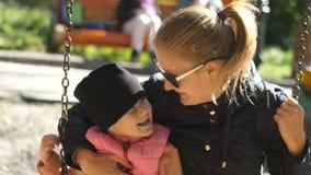 Το παιδί και η μητέρα του οδηγούν σε μια ταλάντευση και παρουσιάζουν γλώσσες τους στο πάρκο ηλιόλουστο ημερησίως φθινοπώρου Οικογ απόθεμα βίντεο