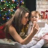 Το παιδί και mom κάνει selfie στο κινητό τηλέφωνο, χριστουγεννιάτικο δέντρο Στοκ Εικόνα