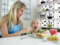 το παιδί καφέδων ταΐζει τη μ στοκ εικόνα