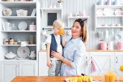 Το παιδί κλείνει το πορτοκάλι ματιών του γύρω από Γιος και νέα μητέρα στην κουζίνα που τρώει το πρόγευμα Στοκ Εικόνα