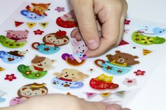 Το παιδί κολλά μια αυτοκόλλητη ετικέττα στο applique Στοκ φωτογραφίες με δικαίωμα ελεύθερης χρήσης