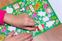 Το παιδί κολλά μια αυτοκόλλητη ετικέττα στο applique Στοκ Εικόνες