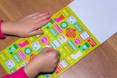 Το παιδί κολλά μια αυτοκόλλητη ετικέττα στο applique Στοκ φωτογραφία με δικαίωμα ελεύθερης χρήσης