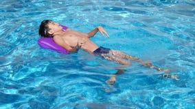 Το παιδί κολυμπά στο διογκώσιμο μαξιλάρι στη λίμνη 4k, σε αργή κίνηση απόθεμα βίντεο