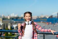 Το παιδί κοριτσιών ακούει μουσική υπαίθρια με τα σύγχρονα ακουστικά Αφουγκραστείτε ελεύθερο Μουσική ρευμάτων οπουδήποτε Πάρτε την στοκ φωτογραφίες