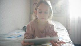 Το παιδί κοριτσιών βάζει διαβασμένο το κρεβάτι βιβλίο Οι μακρυμάλλεις χαριτωμένες πυτζάμες παιδιών κοριτσιών χαλαρώνουν και διαβά απόθεμα βίντεο