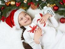 Το παιδί κοριτσιών βρίσκεται στη διακόσμηση Χριστουγέννων γούνα, κινηματογράφηση σε πρώτο πλάνο προσώπου, που ντύνεται στην άσπρη Στοκ Εικόνα
