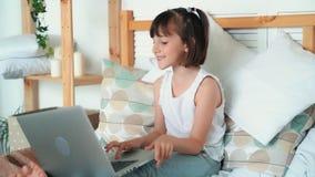 Το παιδί κοριτσιών κάθεται στο κρεβάτι, χρησιμοποιεί το lap-top, λέει συναισθηματικά κάτι, σε αργή κίνηση απόθεμα βίντεο