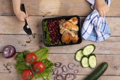 Το παιδί κρατά το εμπορευματοκιβώτιο τροφίμων με τα ψημένα στη σχάρα φτερά κοτόπουλου, μπλε πετσέτα στοκ εικόνα με δικαίωμα ελεύθερης χρήσης