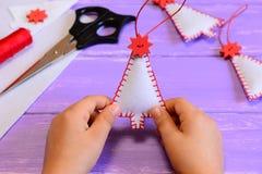 Το παιδί κρατά μια αισθητή διακόσμηση χριστουγεννιάτικων δέντρων στα χέρια του Γίνοντες παιδί διακοσμήσεις Χριστουγέννων από αισθ Στοκ Εικόνες