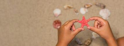 Το παιδί κρατά τον κόκκινο αστερία αμμώδη κοχύλια θάλασσας παραλιών Θερινή πλάτη Στοκ Εικόνες