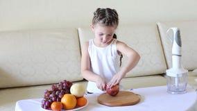Το παιδί κόβει τα μήλα με ένα μαχαίρι απόθεμα βίντεο