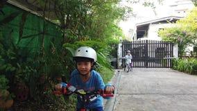 Το παιδί μαθαίνει να οδηγά ένα ποδήλατο με την πλήρη προστασία φιλμ μικρού μήκους