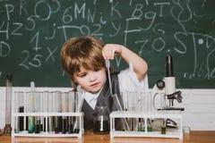 Το παιδί μαθαίνει στην κατηγορία στο υπόβαθρο του πίνακα r r Παιδί από το δημοτικό σχολείο bipeds στοκ εικόνες