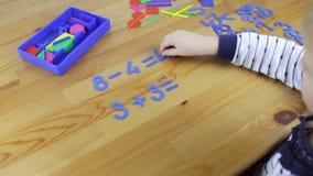 Το παιδί μελετά την αριθμητική, λύνει τα παραδείγματα φιλμ μικρού μήκους
