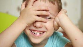 Το παιδί με τη χαρά και το χαμόγελο εξετάζει τη κάμερα, κρατώντας τα χέρια του πίσω από το κεφάλι του, κινηματογράφηση σε πρώτο π απόθεμα βίντεο