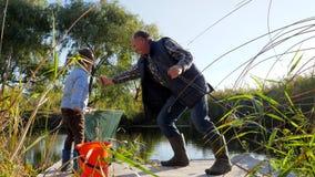 Το παιδί με το granddad αλιεύει στη λίμνη στον καλό καιρό μεταξύ των δέντρων και της χλόης απόθεμα βίντεο