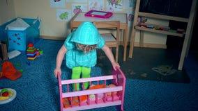 Το παιδί μικρών παιδιών καθορίζει το μωρό παιχνιδιών - κούκλα και ταλάντευση στο κρεβάτι παχνιών απόθεμα βίντεο