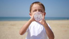 Το παιδί πίνει το νερό από ένα διαφανές πλαστικό μπουκάλι, και έπειτα τα χαμόγελα στην αμμώδη παραλία θάλασσας φιλμ μικρού μήκους
