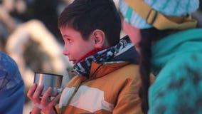 Το παιδί πίνει το τσάι κοντά στην πυρκαγιά, και οι ενήλικοι του λένε μια ιστορία απόθεμα βίντεο
