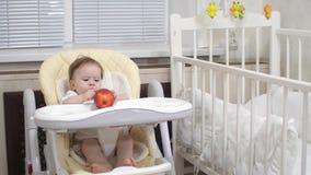 Το παιδί παίζει με την κόκκινη συνεδρίαση μήλων στην καρέκλα στοκ εικόνες με δικαίωμα ελεύθερης χρήσης