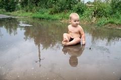 Το παιδί παίζει σε μια μεγάλη βρώμικη λακκούβα παιδική ηλικία ευτυχής Στοκ Φωτογραφίες