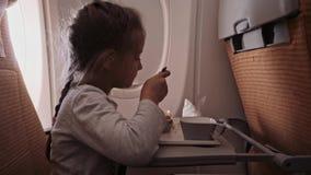 Το παιδί πετά σε ένα αεροπλάνο για να στηριχτεί τη συνεδρίαση κοριτσιών Α κοντά στο παράθυρο και να φάει απόθεμα βίντεο