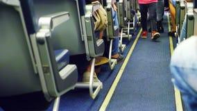 Το παιδί που περπατά μέσω της καμπίνας του αεροπλάνου μόνο τα πόδια είναι ορατά, εσωτερικός του αεροπλάνου με τους επιβάτες στα κ απόθεμα βίντεο