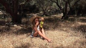 Το παιδί που τρώει τα σταφύλια, πεινασμένο μικρό κορίτσι της Farmer τρώει τα φρούτα στον οπωρώνα 4K ελιών φιλμ μικρού μήκους