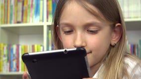 Το παιδί που χρησιμοποιεί την ταμπλέτα που ψάχνει τα βιβλία, παιδί στη βιβλιοθήκη, μελέτη σπουδαστών κοριτσιών, μαθαίνει απόθεμα βίντεο