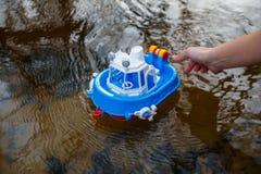 Το παιδί προωθεί μια βάρκα στο δασικό ποταμό στοκ εικόνες