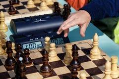 Το παιδί πρόκειται να κάνει μια κίνηση σε ένα παιχνίδι σκακιού στοκ εικόνες