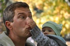 Το παιδί σε μια μέντα ΚΑΠ άρπαξε τον πατέρα της από τη μύτη στοκ φωτογραφίες με δικαίωμα ελεύθερης χρήσης