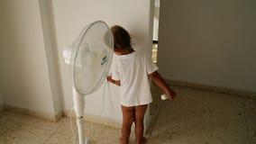 Το παιδί στέκεται κοντά στον ανεμιστήρα απόθεμα βίντεο