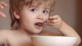 Το παιδί στην κουζίνα στην επιτραπέζια κατανάλωση m Το εύθυμο παιδί μωρών τρώει τα τρόφιμα τα ίδια με το κουτάλι Ευτυχές μωρό απόθεμα βίντεο