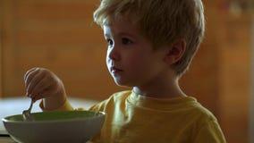 Το παιδί στην κουζίνα στην επιτραπέζια κατανάλωση m Το εύθυμο παιδί μωρών τρώει τα τρόφιμα τα ίδια με το κουτάλι απόθεμα βίντεο