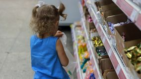 Το παιδί στην υπεραγορά αγοράζει τις καραμέλες και τα γλυκά Κατάστημα αγορών απόθεμα βίντεο