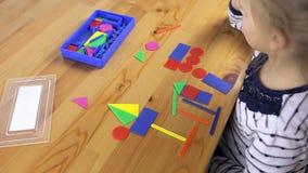 Το παιδί συλλέγει τα αντικείμενα από τις γεωμετρικές μορφές απόθεμα βίντεο