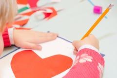 Το παιδί σύρει μια κάρτα Τα παιδιά συμμετέχουν στη ραπτική Το κορίτσι υπογράφει μια κάρτα στις 14 Φεβρουαρίου Στοκ εικόνα με δικαίωμα ελεύθερης χρήσης