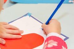Το παιδί σύρει μια κάρτα Τα παιδιά συμμετέχουν στη ραπτική Το κορίτσι υπογράφει μια κάρτα στις 14 Φεβρουαρίου Στοκ Φωτογραφίες