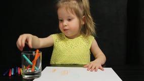 Το παιδί τριάχρονων παιδιών σύρει με τα χρωματισμένα μολύβια και χαμογελά σε μια κίτρινη μπλούζα απόθεμα βίντεο