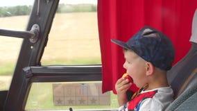 Το παιδί τρώει ένα μήλο στο λεωφορείο απόθεμα βίντεο