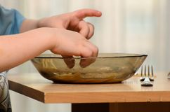 Το παιδί τρώει τη σούπα με τα χέρια του, μπορείτε να δείτε τον πίνακα καλύπτετε και τα χέρια αγοριών ` s στοκ εικόνα