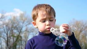 Το παιδί φυσά τις φυσαλίδες σαπουνιών ενάντια στο μπλε ουρανό φιλμ μικρού μήκους