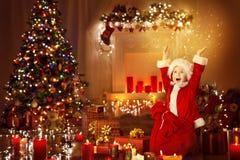 Το παιδί Χριστουγέννων ευτυχές παρουσιάζει τα δώρα, παιδί που ανοίγει τα παρόντα παιχνίδια Στοκ φωτογραφία με δικαίωμα ελεύθερης χρήσης